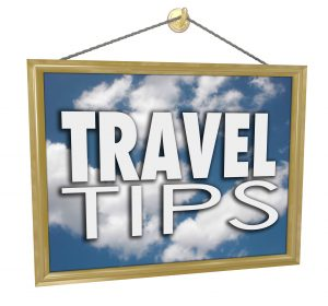 Pest control travel advice - Travel Tips words on a hanging sign with clouds in blue sky advertising helpful tips, advice and information